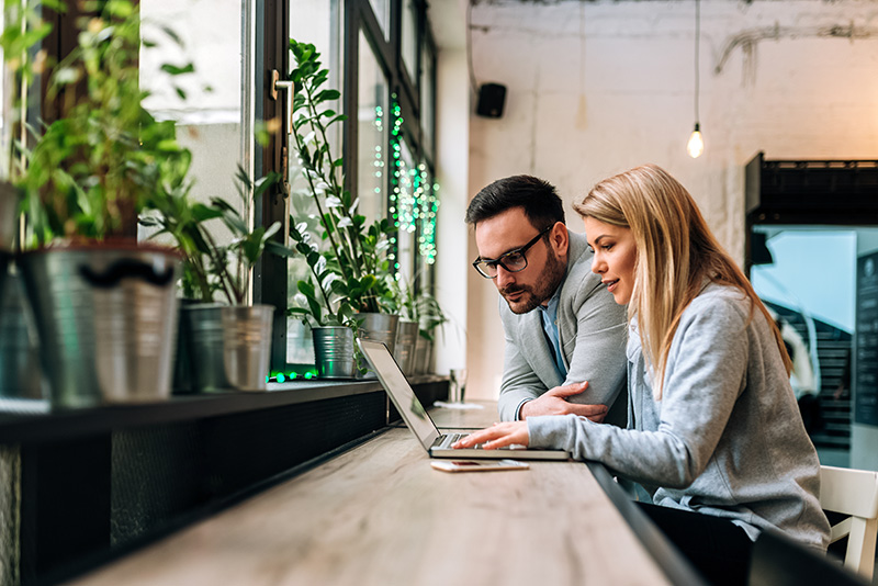 O femeie și un bărbat care lucrează la laptop