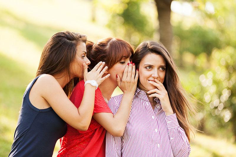 Girls whispering on each other ear